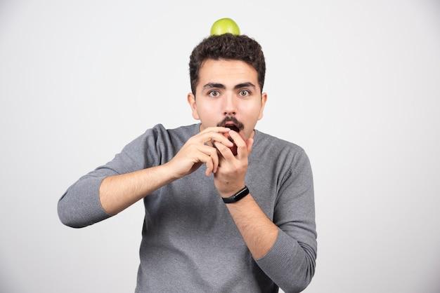 Un homme affamé veut manger de la pomme sur fond gris.