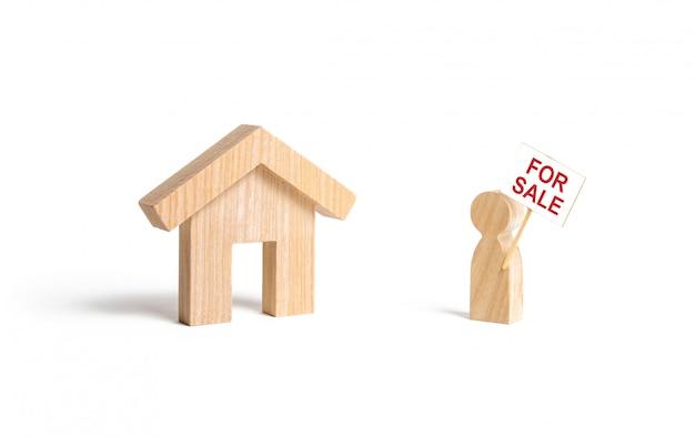 Un homme avec une affiche à vendre se tient près de la maison