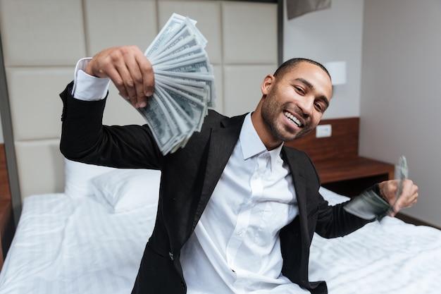 Homme africain avec de l'argent dans les mains assis sur le lit dans la chambre d'hôtel et regardant la caméra