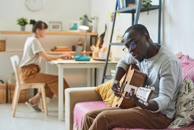 Homme africain assis sur un canapé et jouant de la guitare avec une femme assise à la table en arrière-plan