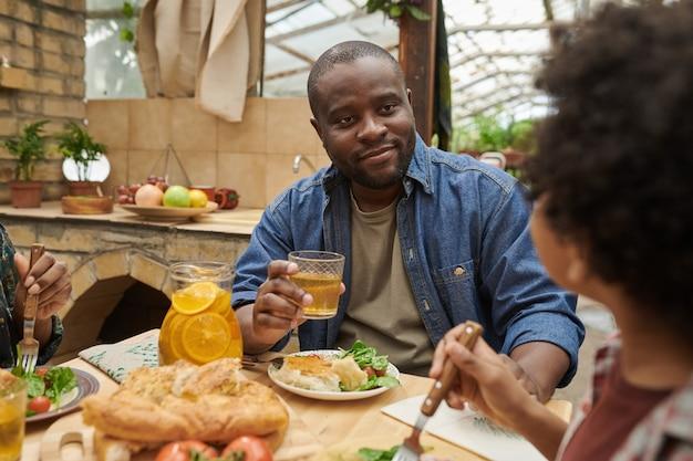 Homme africain assis à table et dînant avec sa famille à la maison