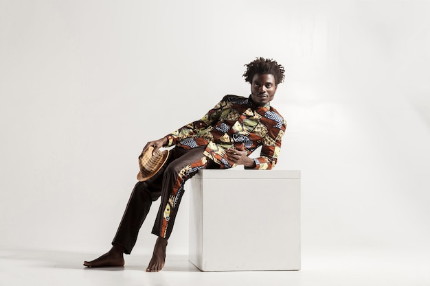 Homme africain aux pieds nus inconfortable s'asseoir sur un cube. intérieur, isolé sur fond gris
