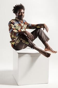 Homme africain célèbre et à la mode posant sur cube. intérieur, isolé sur fond gris