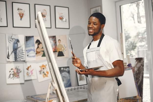 Homme africain en classe de peinture dessin sur un chevalet.