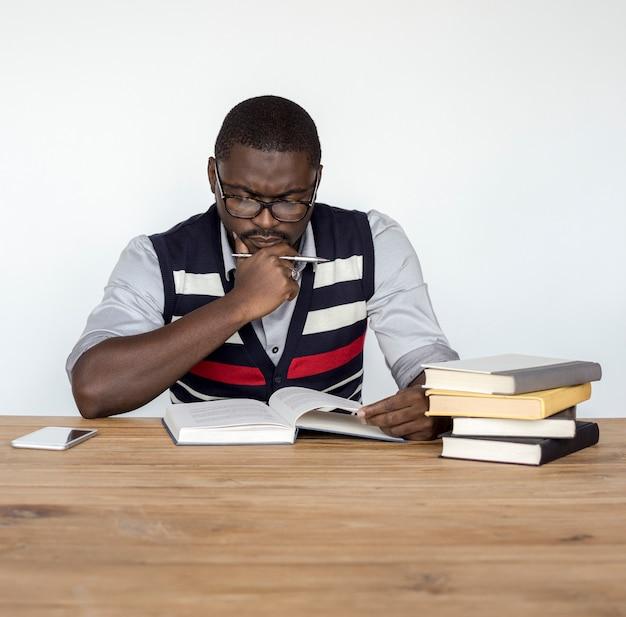 Homme africain curieux pensant lecture livre portrait en studio
