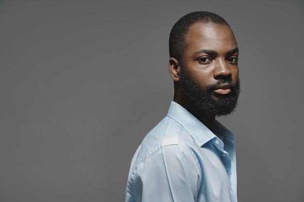 Homme africain dans un studio. mur blanc. homme en chemise bleue.