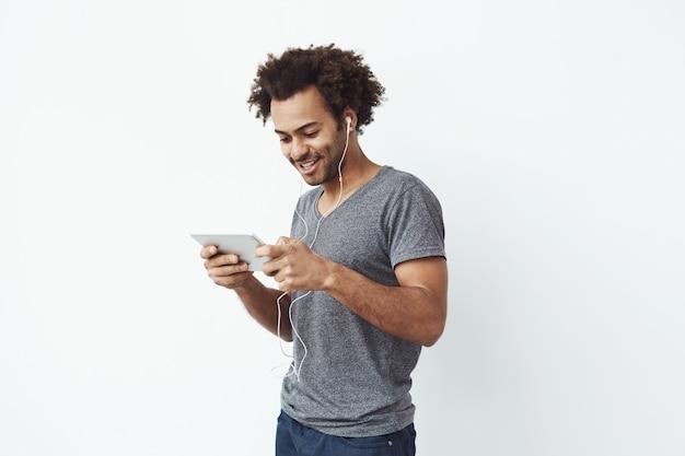 Homme africain drôle dans les écouteurs souriant rire en regardant la tablette.