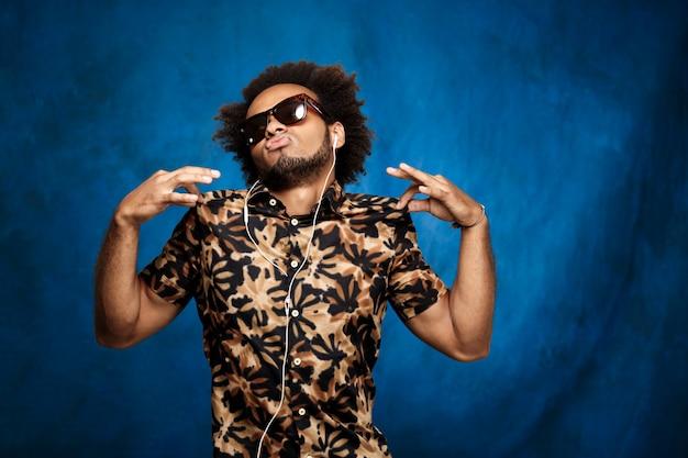 Homme africain, écouter de la musique dans les écouteurs, danser sur le mur bleu.