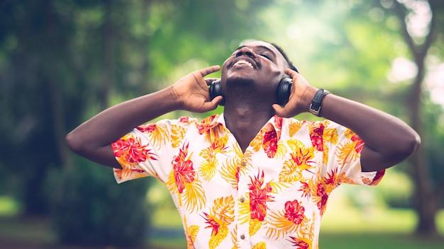 Homme africain, écouter de la musique de smartphone avec des écouteurs contre vert naturel.