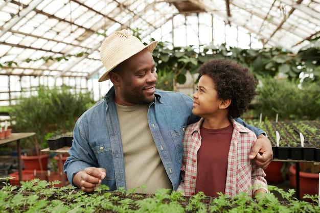 Homme africain embrassant un enfant et lui parlant pendant la plantation de semis en serre