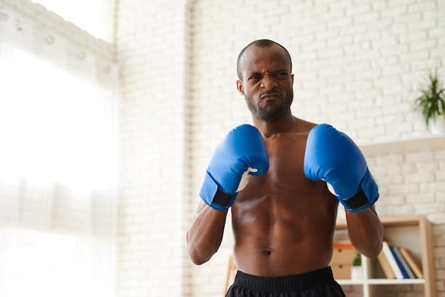 Homme africain enragé dans des gants de boxe.