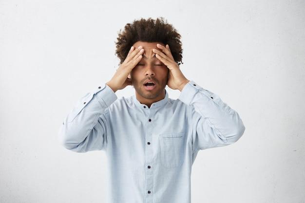 Homme africain épuisé avec des cheveux touffus ayant des maux de tête debout avec les yeux fermés
