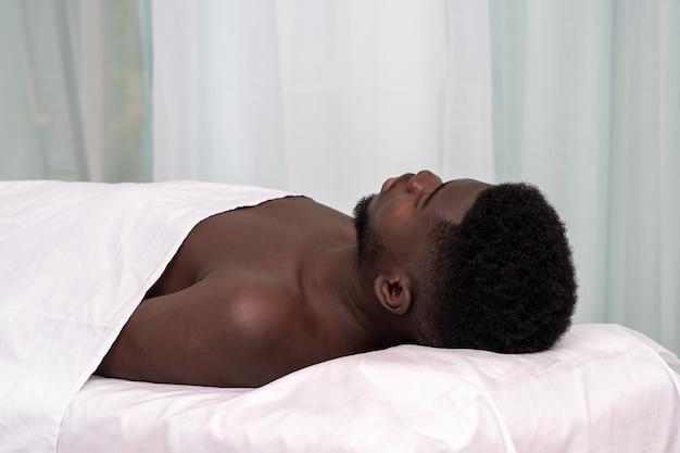 L'homme africain est allongé sur un canapé dans un établissement de santé