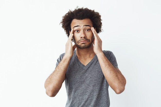 Homme africain fatigué s'ennuie, toucher le visage avec les mains.