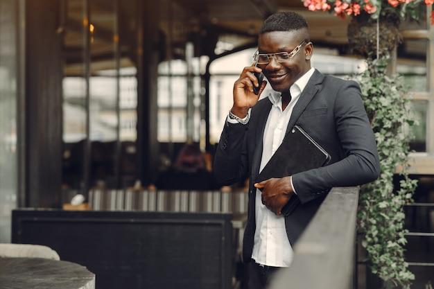 Homme africain. guy en costume noir. homme avec un téléphone portable. homme d'affaires au bureau.