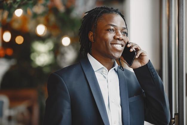 Homme africain. guy en costume noir. homme avec un téléphone portable.
