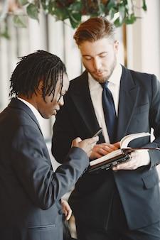 Homme africain. guy en costume noir. des personnes mixtes travaillent ensemble.