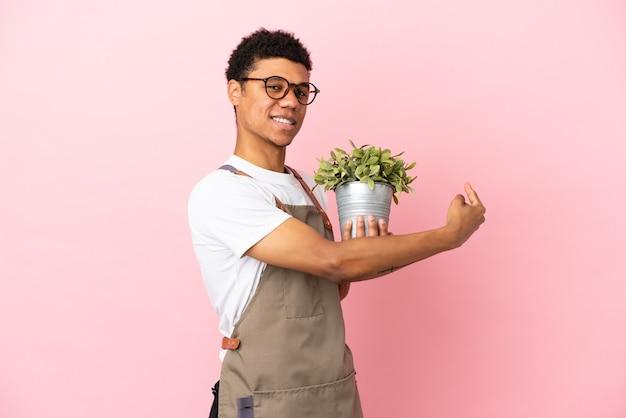 Homme africain de jardinier tenant une plante isolée sur fond rose pointant vers l'arrière