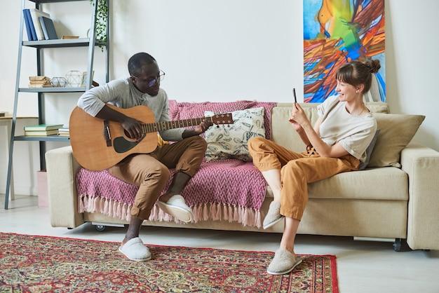 Homme africain jouant de la guitare pendant qu'une femme lui tire dessus sur un téléphone portable alors qu'ils sont assis sur un canapé