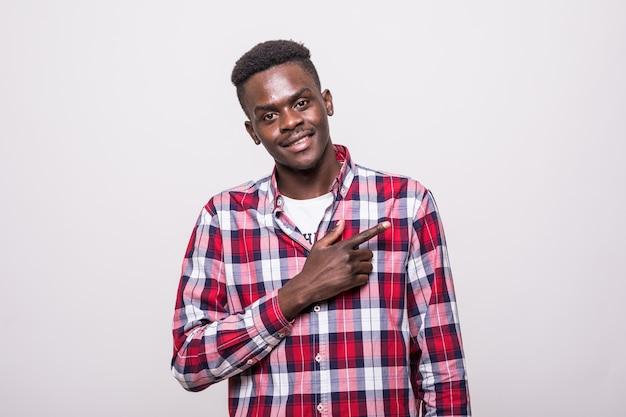 Homme africain joyeux pointant les doigts sur le côté. copiez l'espace.