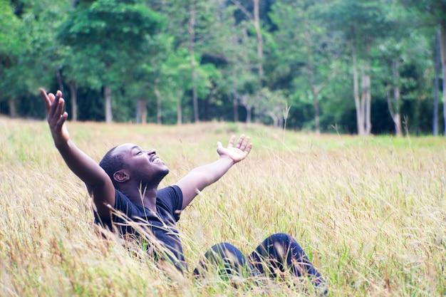 Homme africain de liberté profitant de la nature sur l'herbe