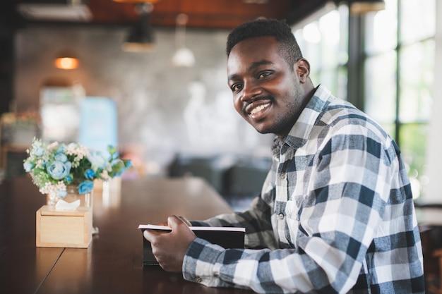 Homme africain lisant un livre dans un café avec le sourire et heureux