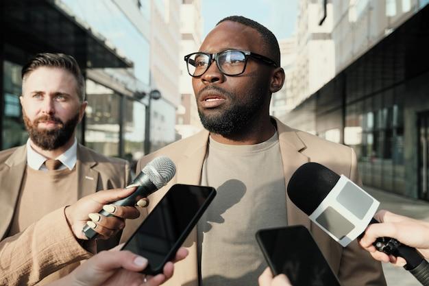 Homme africain à lunettes debout dans la ville parmi les journalistes et donnant une interview