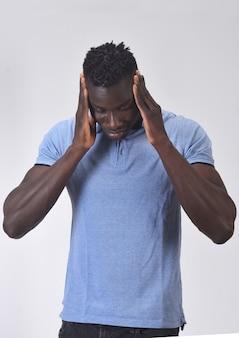 Homme africain avec mal de tête sur fond blanc