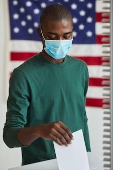 Homme africain en masque de protection mettant le bulletin de vote dans la boîte il vote pendant la pandémie
