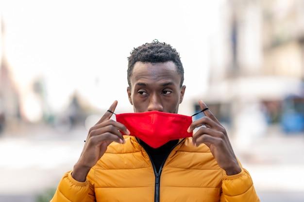 Homme africain mettant sur un masque rouge avec fond de ville floue