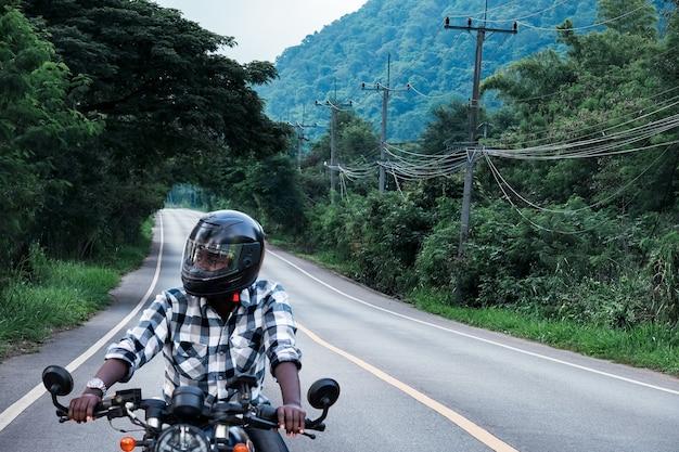 L'homme africain de motard dans le casque conduisant une moto se promène sur la route de l'autoroute