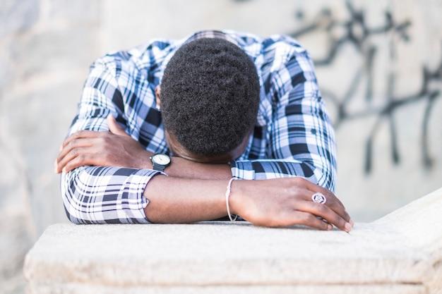 Homme africain noir désespéré avec la tête baissée sur les bras pleurant