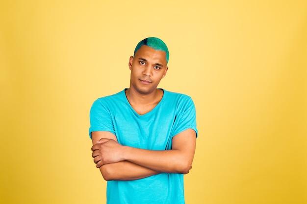 Homme africain noir en tenue décontractée sur mur jaune regarder à la caméra réfléchie avec sourire mains croisées bras