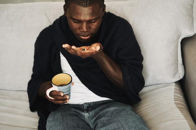 Homme africain avec des pilules à la main une tasse de vêtements sombres santé boisson