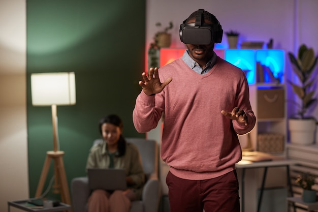 Homme africain portant des lunettes debout dans la pièce et faisant des gestes tout en jouant au jeu de réalité virtuelle