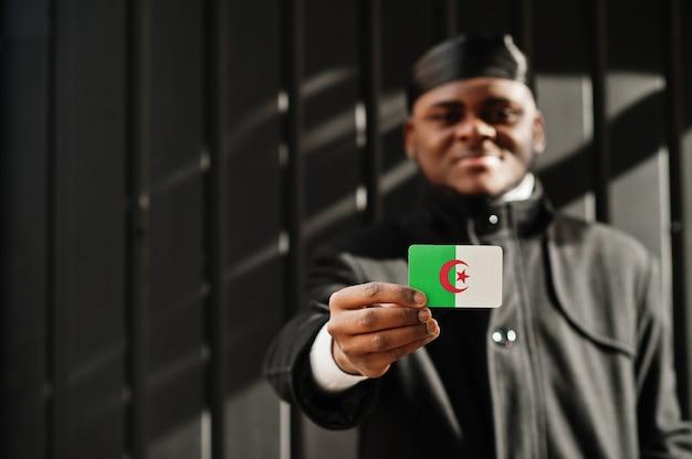 Homme africain porter durag noir tenir le drapeau de l'algérie à la main mur sombre isolé.