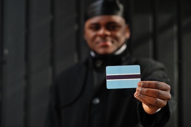 Homme africain porter durag noir tenir le drapeau du botswana à la main mur sombre isolé.