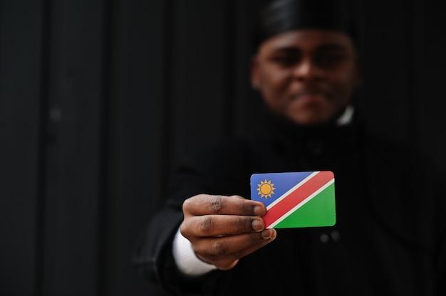 Homme africain porter durag noir tenir le drapeau de la namibie à la main mur sombre isolé.