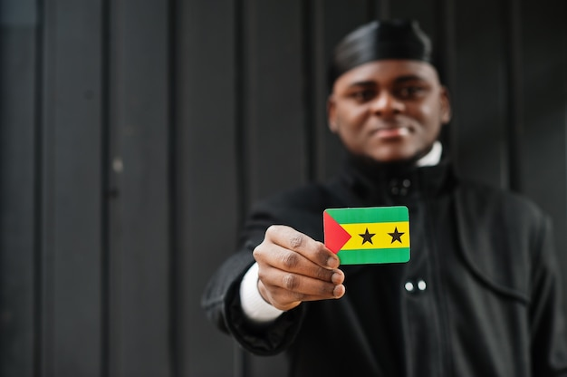 Homme africain porter durag noir tenir le drapeau de sao tomé-et-principe à la main mur sombre isolé.