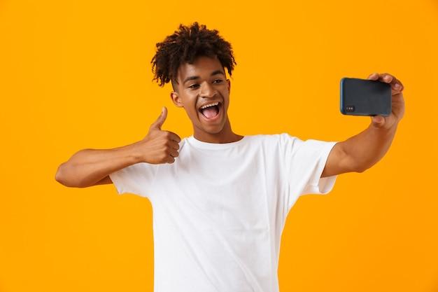 Homme africain posant isolé sur un espace jaune prendre un selfie par téléphone.