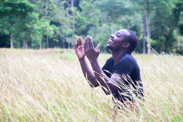 Homme africain priant pour remercier dieu avec une lumière parasite dans un pré.