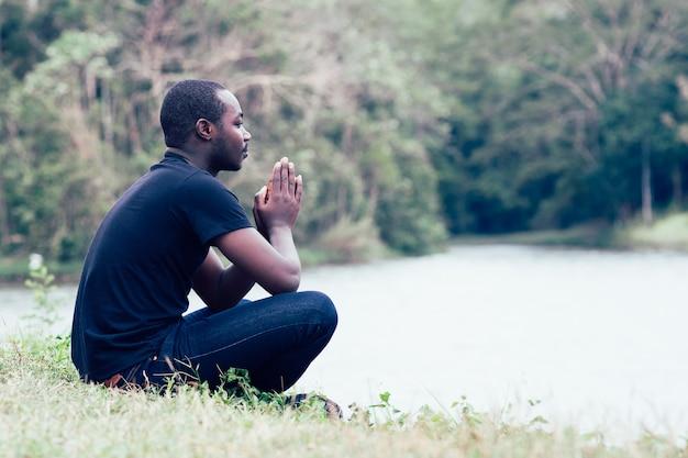 Homme africain priant pour remercier dieu avec la nature verte en arrière-plan.