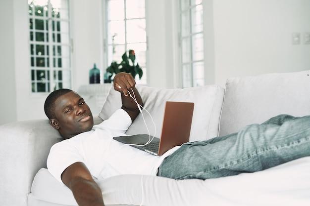 Homme africain à la recherche d'un ordinateur portable sur le canapé à l'intérieur