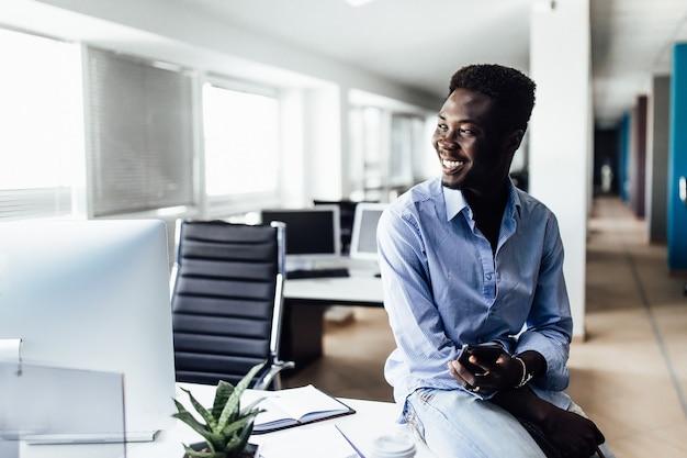 Homme africain réussi travaillant dans un centre de bureau légèrement et souriant.