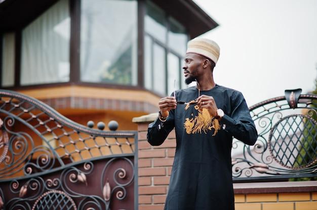 Homme africain riche en vêtements traditionnels élégants et chapeau posé fond extérieur son manoir.