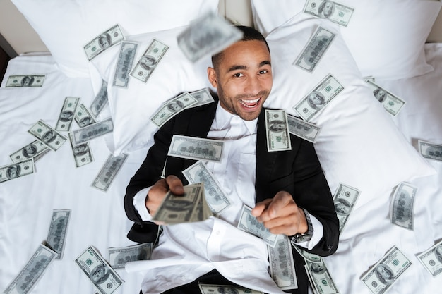 Homme africain souriant en costume allongé sur le lit dans la chambre d'hôtel avec de l'argent qui tombe et regardant la caméra. vue de dessus