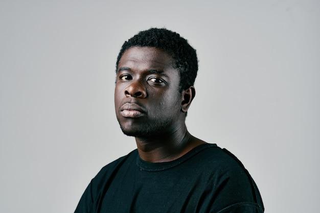Homme africain en studio de mode tshirt noir posant en gros plan