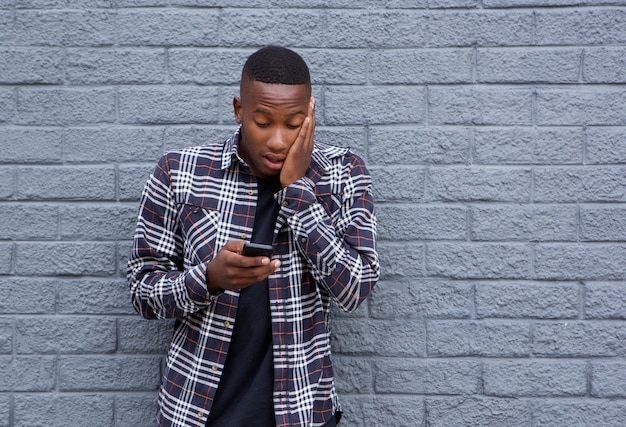 Homme africain surpris en lisant un message texte