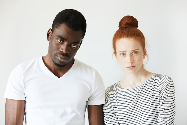 Homme africain en t-shirt blanc et femme de race blanche rousse en haut rayé