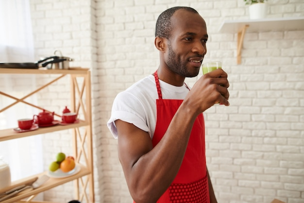 Homme africain en tablier boit du jus de céleri frais à la cuisine.